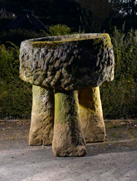 A-large-roughly-hewn-circular-carved-stone-trough-on-staddlestone-supports