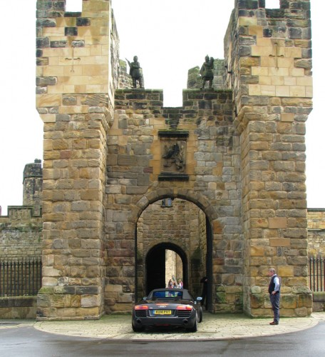 Audi R8 Spyder entering Alnwick Castle through the main gates of the Barbican