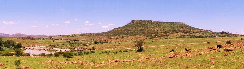 View of Shiyane Mountain: Isandlwana on the skyline above the Buffalo River and Rorke's Drift Mission Station in the trees at the right