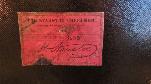 Red label affixed to inside of mahogany brass bound Jaques chess set box