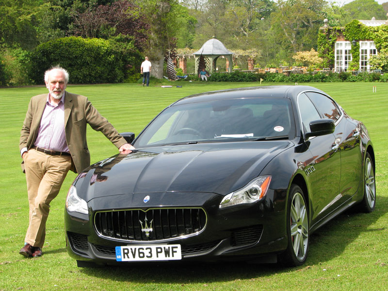 Robert Jarman posing next to the Maserati Quattroporte in the grounds of Chewton Glen