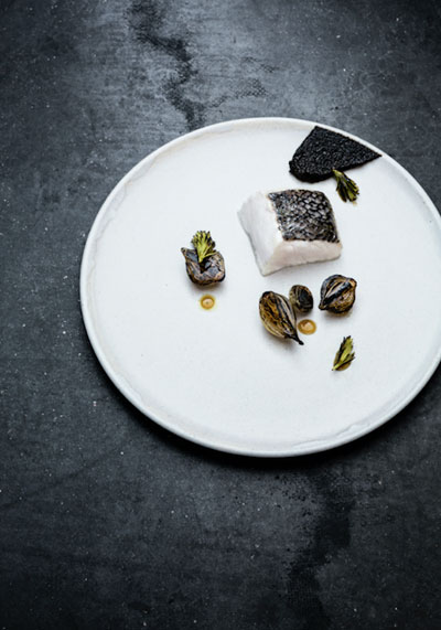 Slow baked hake with burned onion puree and pickled onions by chef Petter Nilsson